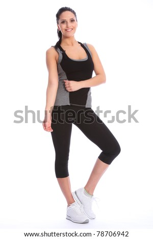 Fit beautiful and young athletic woman standing in a relaxed pose, big smile and wearing a grey and black sports outfit with white trainers. - stock photo