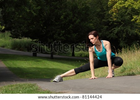 Fit beautiful young athletic woman crouching in the park doing warm up stretch. She is wearing black jogging leggings and blue sports vest outfit.