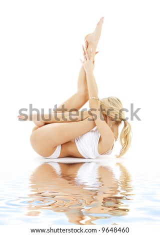 fit blond in white underwear practicing yoga on white sand - stock photo