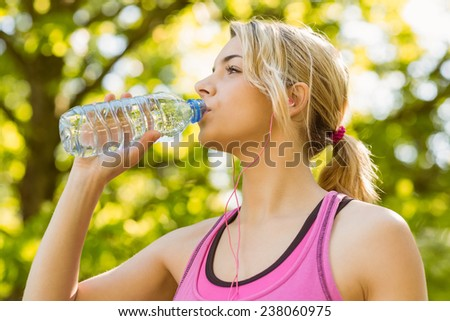 Fit blonde drinking from her water bottle on a sunny day - stock photo
