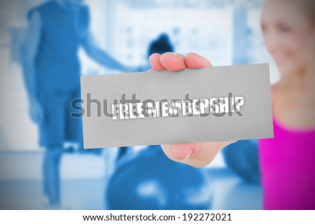 Fit blonde holding card saying free membership against trainer and client in fitness studio - stock photo
