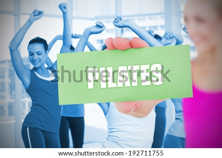 Fit blonde holding card saying pilates against fitness class in gym - stock photo