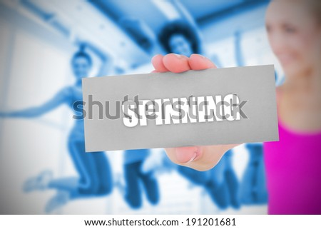 Fit blonde holding card saying spinning against class in gym - stock photo