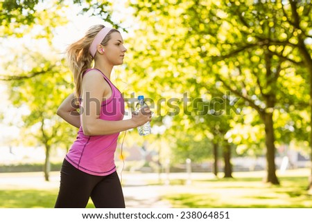 Fit blonde jogging in the park on a sunny day - stock photo