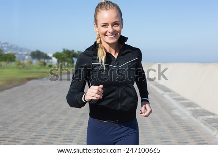 Fit blonde jogging on the pier on a sunny day - stock photo