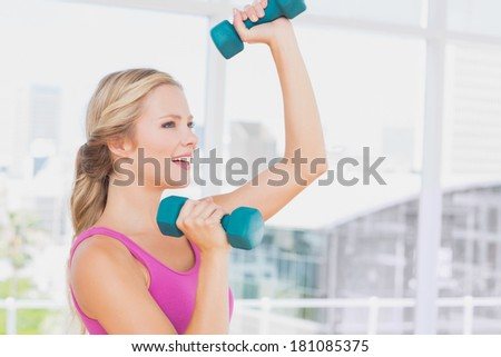 Fit blonde lifting dumbbells and smiling at home in the living room - stock photo