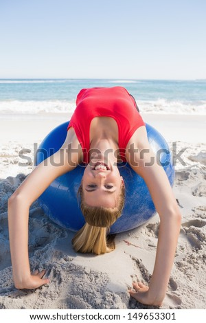 Fit blonde stretching back on exercise ball smiling at camera on the beach - stock photo