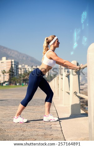 Fit blonde stretching on the pier against fitness interface - stock photo