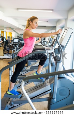 Fit blonde using the step machine at the gym
