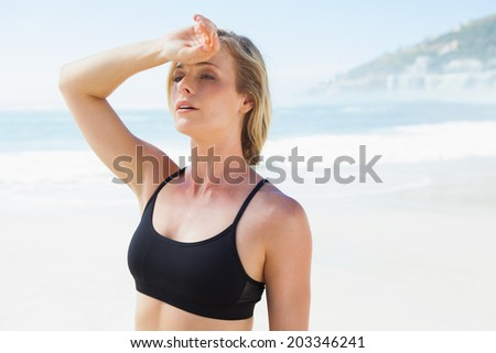 Fit blonde wiping her forehead on the beach on a sunny day