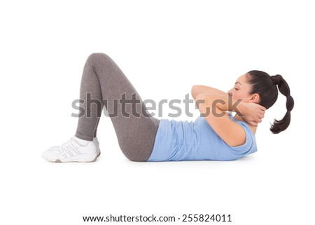 Fit brunette doing sit ups on white background
