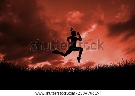 Fit brunette running and jumping against red sky over grass