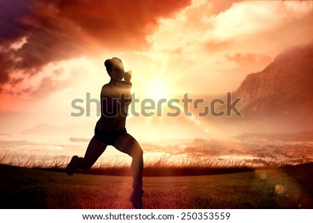 Fit brunette running and jumping against sunrise over magical sea