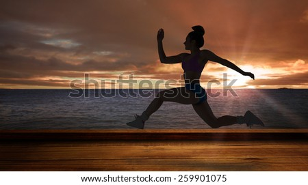 Fit brunette running and jumping against wooden planks against sea