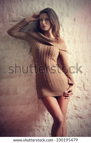 fit brunette sexy woman posing with  wool short dress and perfect nude legs, long hair looking in camera. Autumn, winter concept