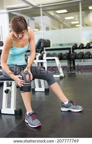 Fit brunette sitting on bench holding injured knee at the gym - stock photo