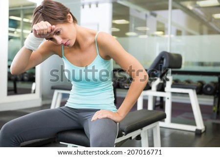 Fit brunette sitting on bench wiping forward at the gym - stock photo