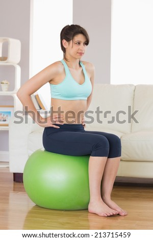 Fit brunette sitting on exercise ball at home in the living room - stock photo
