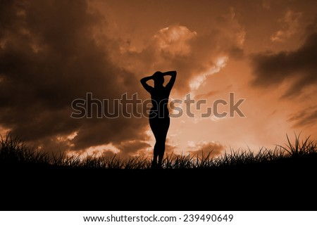 Fit brunette smiling at camera against cloudy sky - stock photo