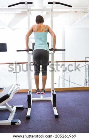 Fit brunette supporting her weight on bars at the gym