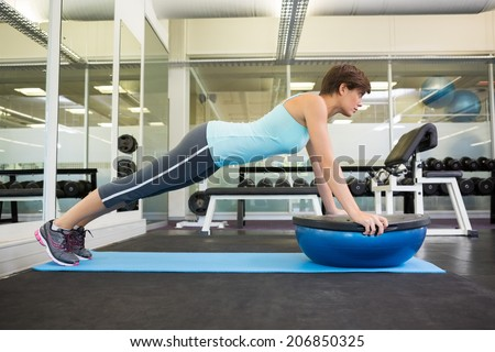Fit brunette using bosu ball in plank position at the gym - stock photo