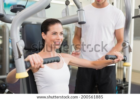 Fit brunette using weights machine for arms with trainer helping at the gym - stock photo