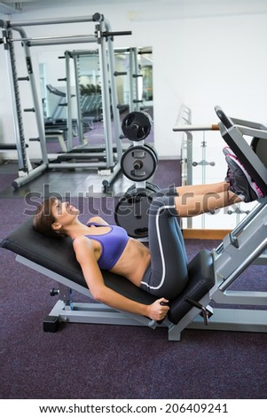 Fit brunette using weights machine for legs at the gym - stock photo