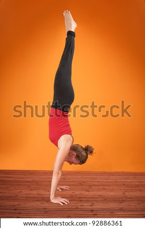 Fit Caucasian woman performs Adho Mukha Vriksasana posture - stock photo