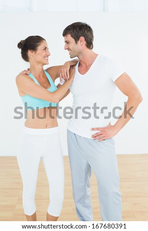 Fit cheerful young couple standing in fitness studio - stock photo