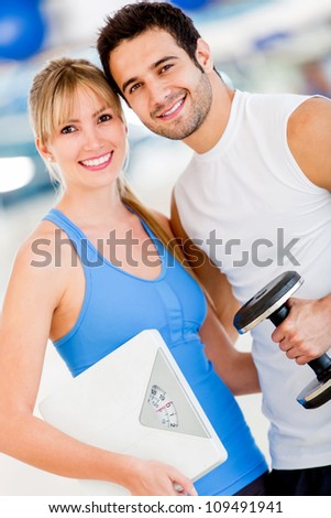 Fit couple at the gym holding a weight scale - stock photo
