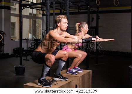 Fit couple doing squats on boxes - stock photo