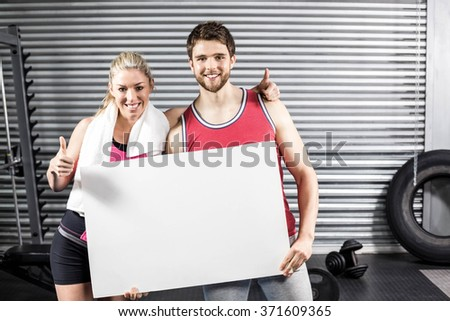Fit couple holding blank paper at crossfit gym - stock photo