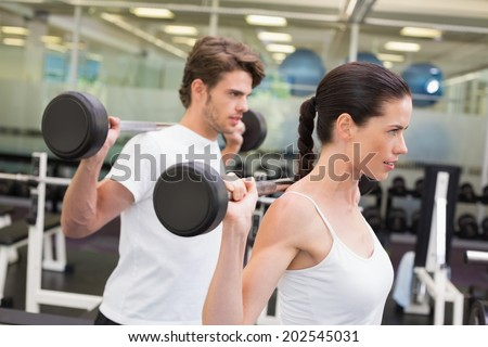 Fit couple lifting barbells together at the gym - stock photo