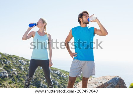 Fit couple standing drinking from water bottles on a sunny day - stock photo