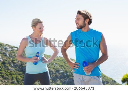 Fit couple standing holding water bottles on a sunny day