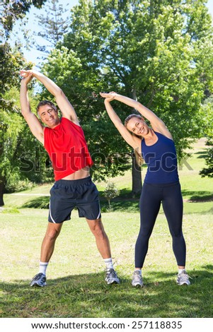 Fit couple stretching in the park on a sunny day