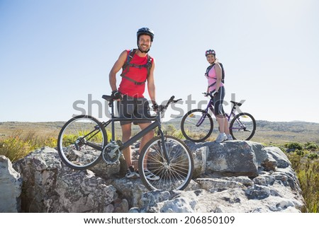 Fit cyclist couple standing at the summit smiling at camera on a sunny day