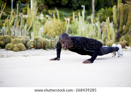 Fit dark skinned man in active clothes doing push-ups exercise outdoors, sporty black man training outside - stock photo