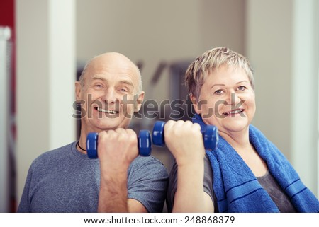 Fit elderly couple working out with weights each holding a dumbbell in a flexed hand as they tone their muscles and looking at the camera with happy smiles