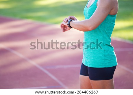 Fit female athlete looking at her watch with a heart rate monitor built in to track her progress of her exercise on a tartan athletics track. - stock photo