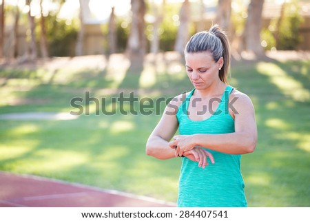 Fit female athlete looking at her watch with heart rate monitor built in to track her progress of her exercise on a tartan athletics track. - stock photo