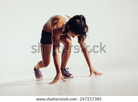 Fit female athlete ready to run over grey background. Female fitness model preparing for a sprint. - stock photo