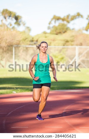 Fit female athlete spring on a tartan athletics track in the late afternoon. - stock photo