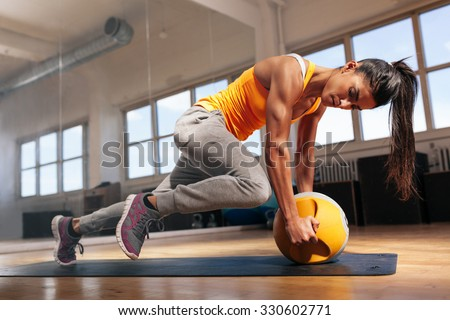 Fit female doing intense core workout in gym. Young muscular woman doing core exercise on fitness mat in health club. - stock photo
