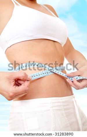 fit female measuring her waist - weight loss series - stock photo