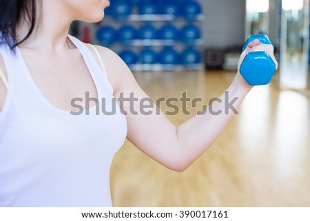 Fit fitness girl smiling happy lifting weights in gym