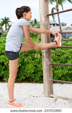 Fit fitness woman doing stretching exercises outdoors on beach. Girl doing hamstring leg stretching exercise and stretches. Female sports model exercising outdoor in summer. Beautiful Asian girl. - stock photo
