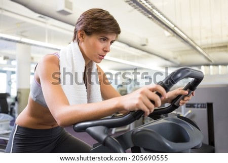 Fit focused brunette working out on the exercise bike at the gym - stock photo