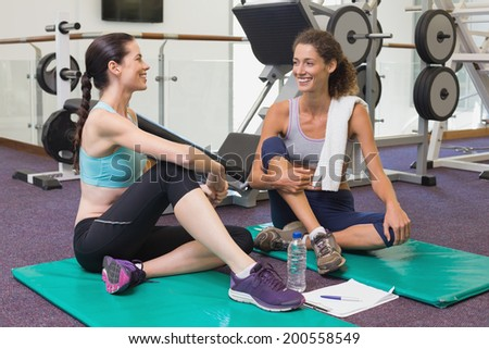 Fit friends chatting together on exercise mats at the gym