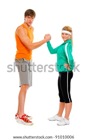 Fit girl and man in sportswear  shaking hands - stock photo